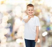 advertising, gesture, people and childhood concept - smiling boy in white blank t-shirt pointing fin