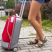 Close-up girls legs and red suitcase outdoors, travel concept.