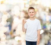 advertising, party, people and childhood concept - smiling little boy in white blank t-shirt making
