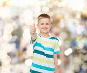 happiness, childhood, holidays, gesture and people concept - smiling little boy showing thumbs up ov