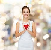 happiness, health, charity and love concept - smiling woman in white dress with red heart over golde