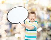 happiness, childhood, conversation and people concept - smiling little boy with blank text bubble ov