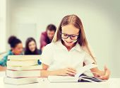 education and school concept - student girl studying and reading books at school