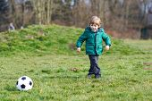 Little Boy Playing Football Or Soccer On Cold Day