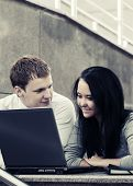 Young business couple using laptop outdoor