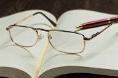 Eye glasses lying on opened blank notepad
