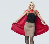 Portrait of beautiful woman in superhero costume over light blue background