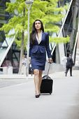 Young Indian businesswoman with luggage on business trip