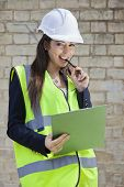 Portrait of a happy female supervisor with clipboard standing at construction site