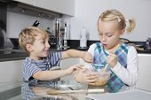 Happy brother and sister mixing batter together in kitchen