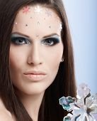 Beauty portrait of young model in professional makeup with rhinestones.