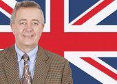 Portrait of smiling middle-aged businessman over British flag