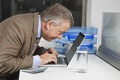 Side view of middle-aged businessman using laptop at desk in office