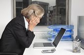 Side view of tired senior businesswoman in front of laptop at desk in office