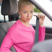 Young attractive lady fastening her seat belt