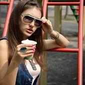 Pretty girl in sunglasses with paper cup of coffee, youth  lifestyle, outdoor portrait. Image toned.