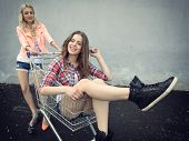Two happy beautiful teen girls driving shopping cart outdoor, Image toned and noise added.