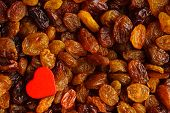 Diet Healthy Food. Raisin As Background Texture And Red Heart