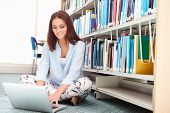 Female College Student Studying In Library With Laptop