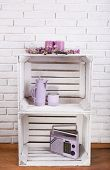 Wooden boxes with home things on white brick wall background