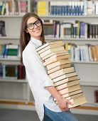 College female student on university campus holding many books in hands