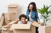 Young Woman Looking At Man Sitting In Cardboard Box