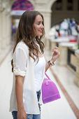 Beautiful young woman in white blouse walks in the shop