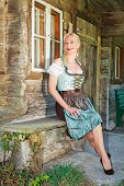blonde woman sitting elegantly in a dirndl