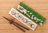 Sushi maki set with fresh sakura branch over bamboo table