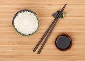 Rice bowl, chopsticks and soy sauce over bamboo table
