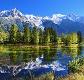 City park in the mountain resort of Chamonix in France. Snowy mountains and evergreen spruce reflect
