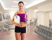 Sporty young girl with skipping rope and scales at gym club