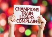 Champions Train Losers Complain card with colorful background with defocused lights