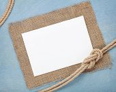 Blank paper card with ship rope over blue wooden background