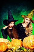 image of teen smoking  - Two pretty teen girls in a costumes of witches standing with pumpkins over dark smoky background - JPG