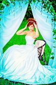 stock photo of wedding arch  - Beautiful bride with chaming red hair sitting under the wedding arch - JPG