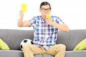Angry football fan holding a yellow card seated on couch isolated against white background