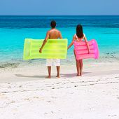 Couple with inflatable rafts on a tropical beach at Maldives