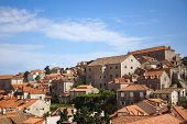 DUBROVNIK, CROATIA - MAY 26, 2014: Old houses inside the city walls with Lokrum island in background. City wall is one of most popular tourist attraction in Dubrovnik.