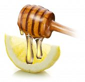 Honey with wood stick pouring onto a slice of lemon. White background.