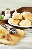 Fresh homemade bread buns from yeast dough on wooden cutting board, on color wooden background