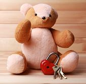 Teddy Bear with padlock in shape of heart on wooden background