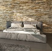 3D Rendering of Modern bed with padded upholstered headboard and footboard in shades of brown against a textured rough stone finish wall in a modern sunlit bedroom interior