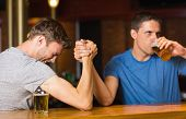 Happy friend arm wrestling each other in a bar