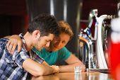 Caring friend comforting upset man at the bar