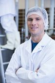 Portrait of a smiling scientist with arms crossed in the factory