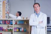 Unsmiling pharmacist standing with arms crossed in the pharmacy