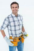 Portrait of confident technician holding spirit level over white background
