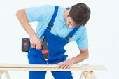 Carpenter using drill machine on wood over white background