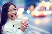 picture of cabs  - Professional young urban casual business woman happy in New York City Manhattan drinking coffee walking in street wearing coat downtown with yellow taxi cabs in background - JPG